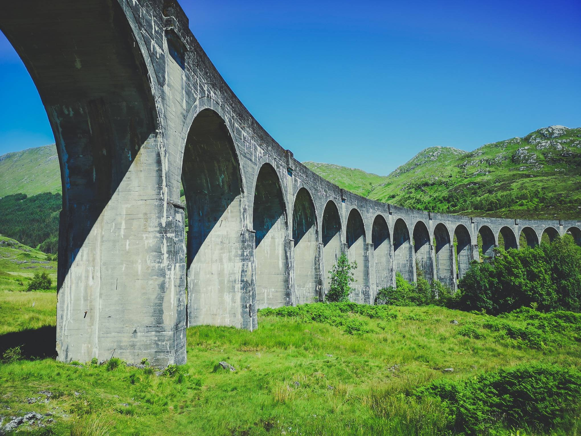 Glenfinnan Viaduct from below on a sunny summer day, Scotland. Photo by Alis Monte [CC BY-SA 4.0], via Connecting the Dots