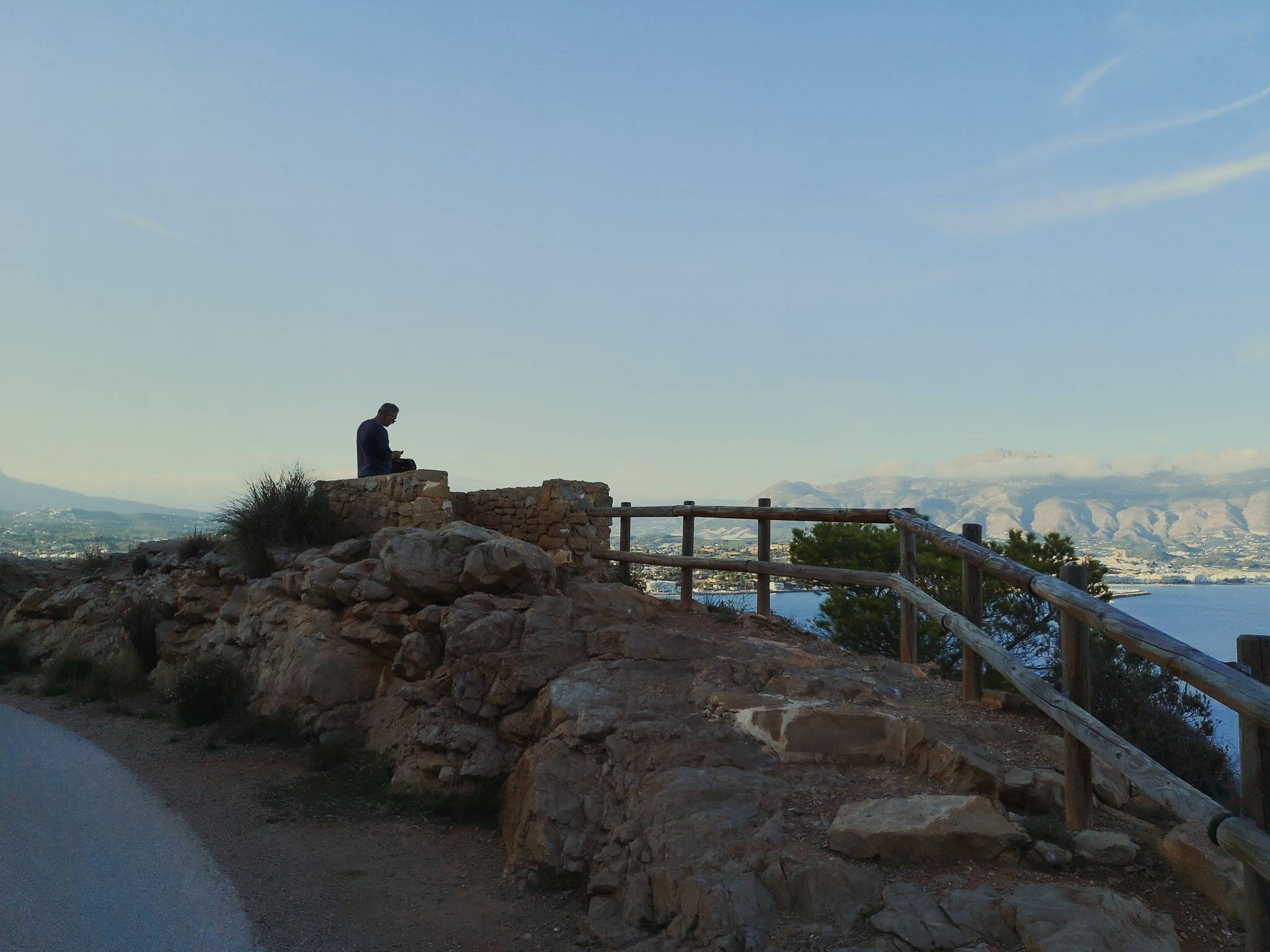 Man sitting on a rock on Camino del Faro. Photo by Alis Monte [CC BY-SA 4.0], via Connecting the Dots