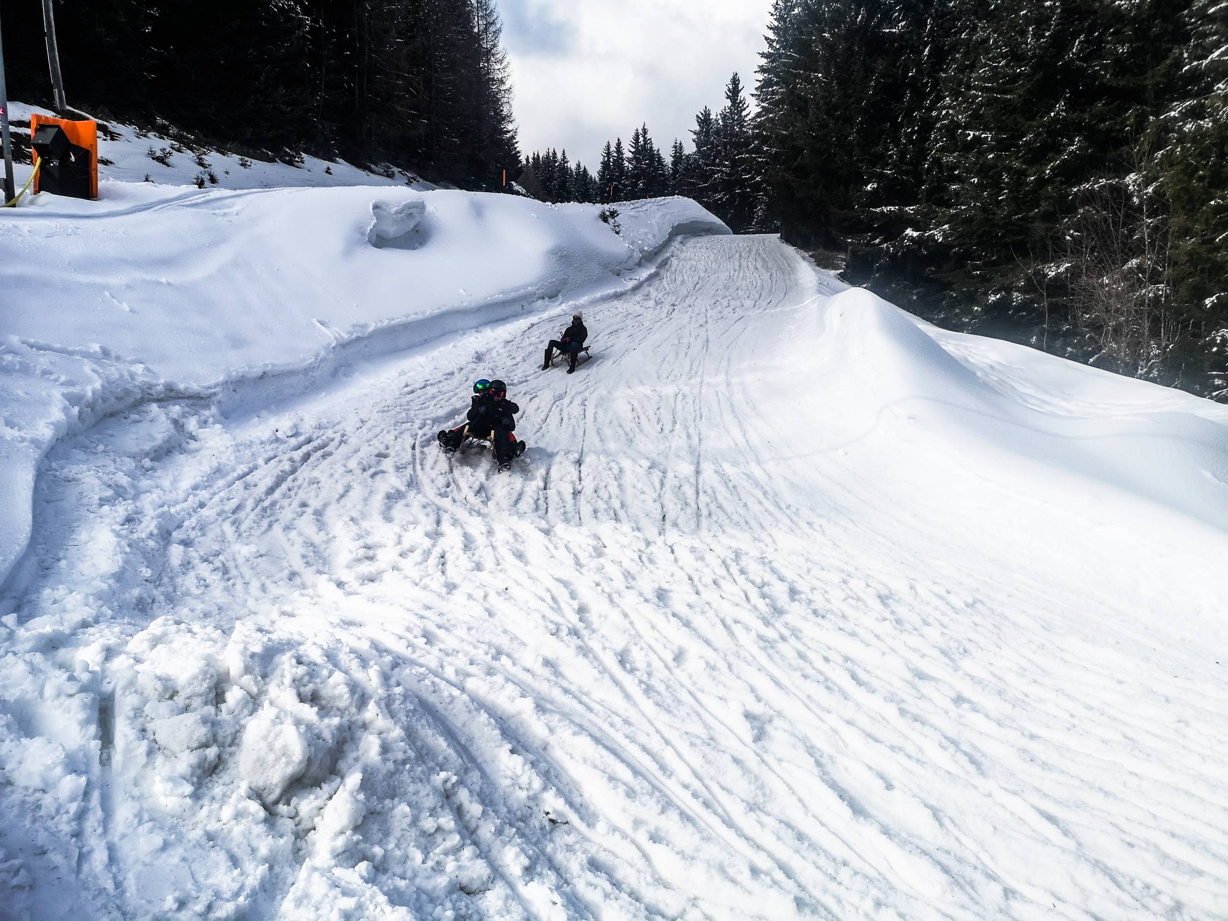Even with your feet on the ground your sled will reach quite a speed. Breaking before any turn is essential. Photo by Alis Monte [CC BY-SA 4.0], via Connecting the Dots